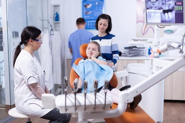 歯の健康上の問題のために痛みを伴う表情で顔に触れている小児歯科医院の少女。歯の間に母親と一緒にいる子供は、椅子に座っている口内検査で診察します。