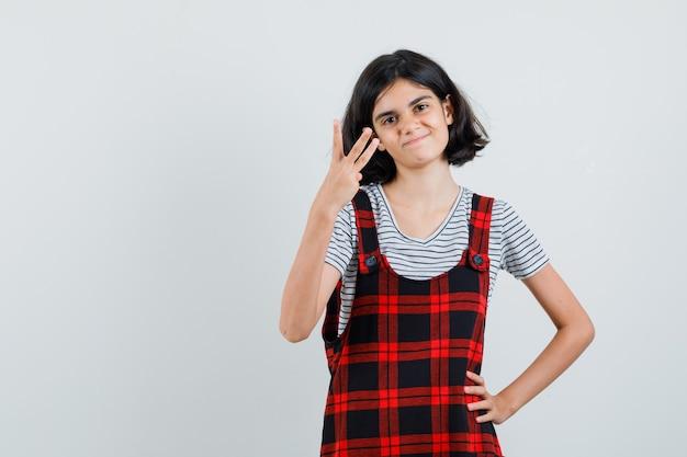 세 손가락을 보여주는 pinafore 드레스에 어린 소녀와 자신감을 찾고,