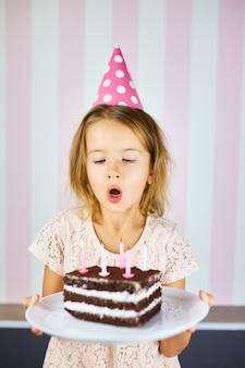 Маленькая девочка в розовой кепке задувает свечи на шоколадном торте на день рождения