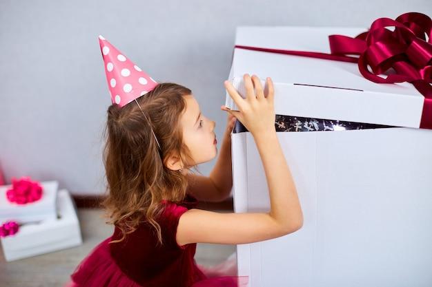 Маленькая девочка в розовом платье и шляпе открыла большую подарочную коробку с воздушными шарами домашний день рождения