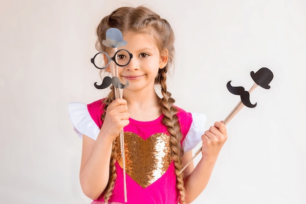 Маленькая девочка в розовом платье, держа маскарадные маски на день отца.