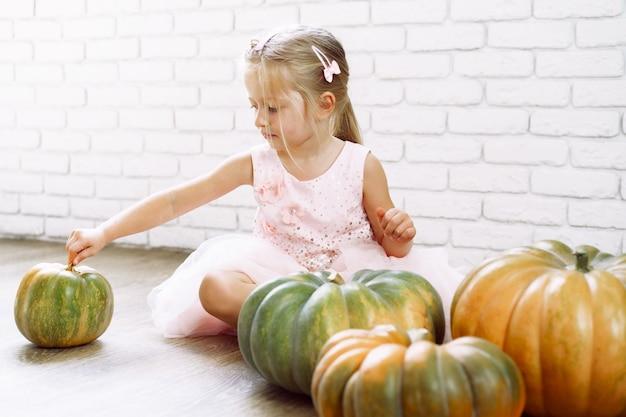 Маленькая девочка в розовом платье сидит на деревянном полу и играет с кучей тыкв