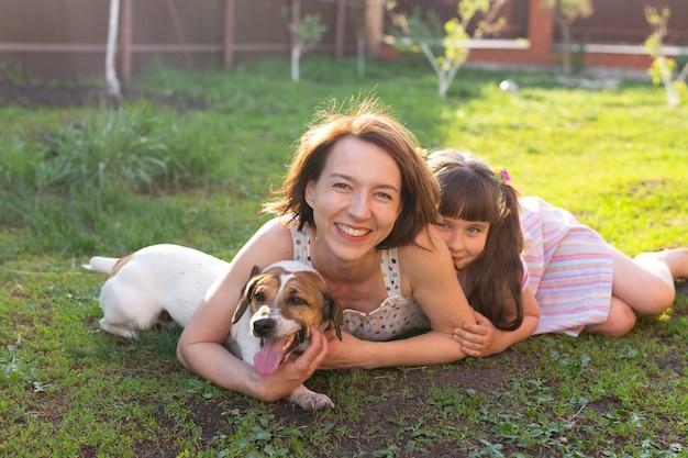 ピンクのドレスを着た少女と母親とジャックラッセルテリア犬が草の上に横たわっています。カメラを見て笑顔