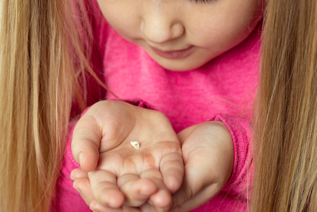 Маленькая девочка в розовом держит в ладонях выпавший молочный зуб. концепция гигиены полости рта.