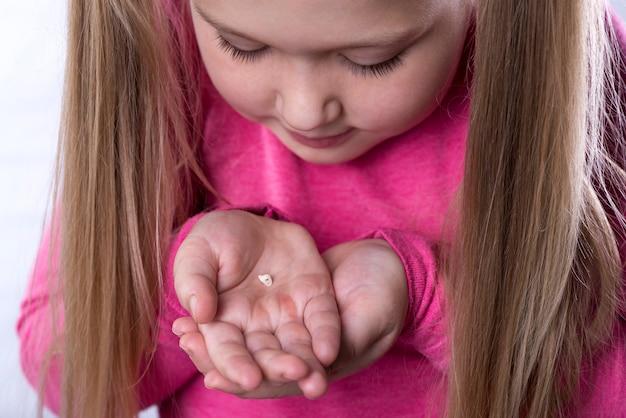 Маленькая девочка в розовом держит в ладонях выпавший молочный зуб