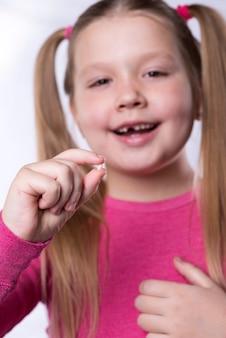 Маленькая девочка в розовом держит выпавший молочный зуб