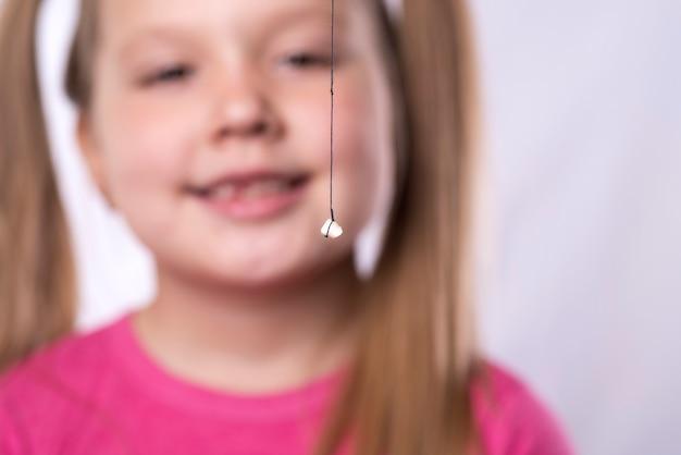 Маленькая девочка в розовом держит на нитке вырванный молочный зуб