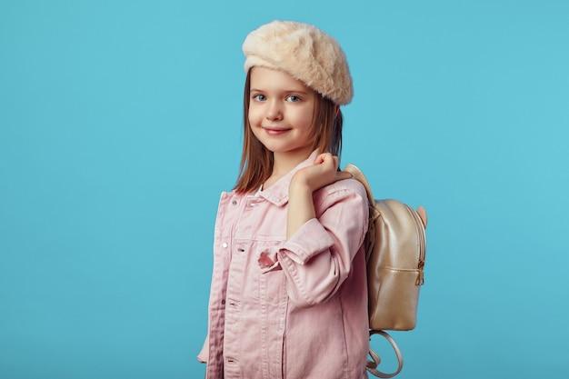 Маленькая девочка в розовой куртке и шляпе улыбается, держа в руке рюкзак