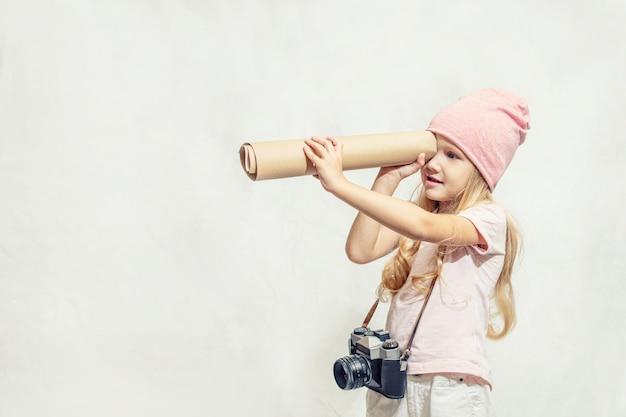 망원경과 흰색 배경에 매달려 카메라와 분홍색 옷을 입은 어린 소녀