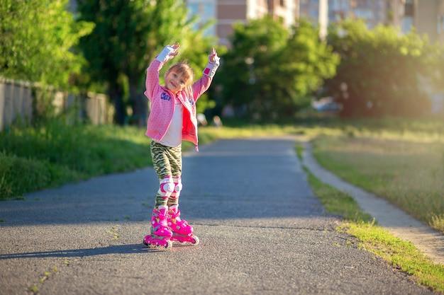 Маленькая девочка в розовых роликах и розовый свитер позирует в парке и улыбается.