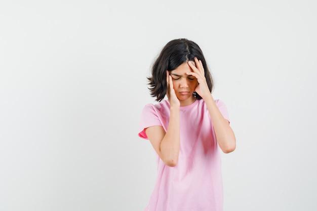 강한 두통이 있고 피곤, 전면보기를 찾고 분홍색 티셔츠에 어린 소녀.