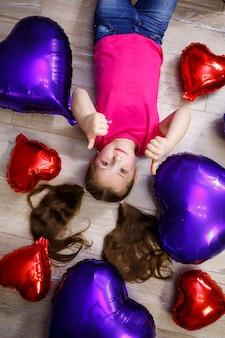 ピンクのtシャツを着た少女が風船で遊ぶ