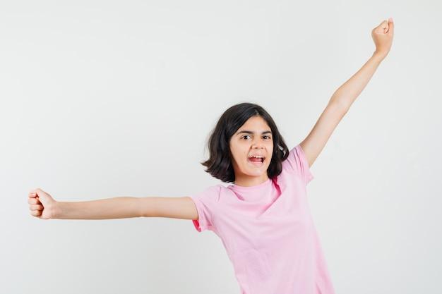 ピンクのtシャツを着た少女が腕を伸ばして幸せそうに見えることで成功のジェスチャーを示しています。正面図。