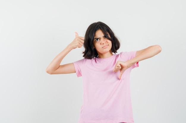 親指を上下に見せて躊躇しているピンクのtシャツを着た少女、正面図。