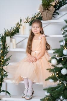 Маленькая девочка в платье принцессы празднует рождество. рождественская волшебная сказка. счастливое детство.