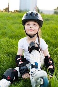 Маленькая девочка в защитном снаряжении и роликах. сидит на траве в парке. молодой счастливый фигурист