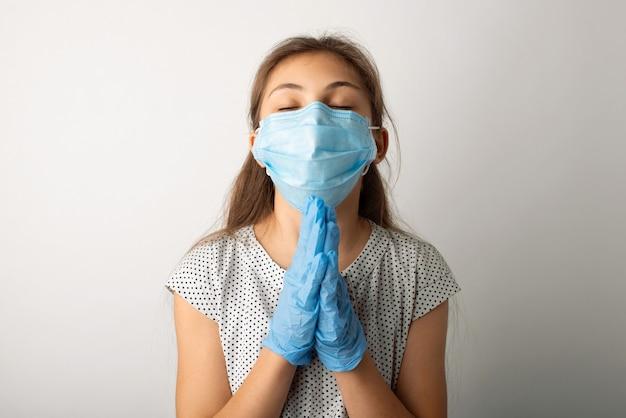 Маленькая девочка в защитной маске и перчатках молится о прекращении пандемии