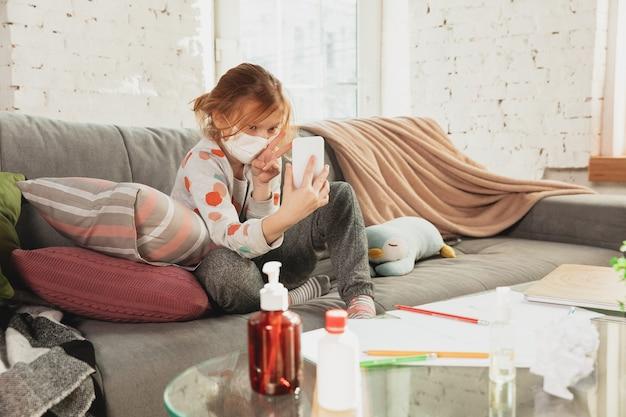 Маленькая девочка в защитной маске изолирована дома с респираторными симптомами коронавируса, такими как лихорадка, головная боль, кашель в легкой форме. чувствует больным.