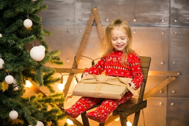 木製の椅子のクリスマスツリーによるパジャマの少女