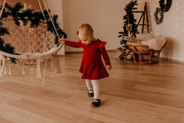 Маленькая девочка в красном платье работает в стиле лёгкого минимализма. ребенок стоит у белой стены с гирляндами рождественская елка с обернутыми подарками. рождество. новогодний интерьер. празднование дня святого валентина