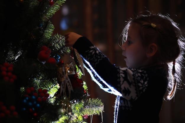 산타 클로스를 기다리는 빨간 모자에 어린 소녀. 즐겁고 밝은 크리스마스. 사랑스러운 아기는 크리스마스를 즐길 수 있습니다. 산타 소녀 어린 아이는 집에서 크리스마스를 축하합니다.