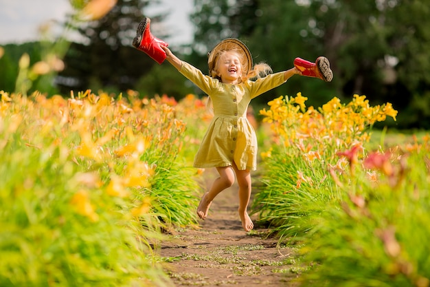 Маленькая девочка в красных резиновых сапогах и соломенной шляпе поливает красные цветы в саду Premium Фотографии