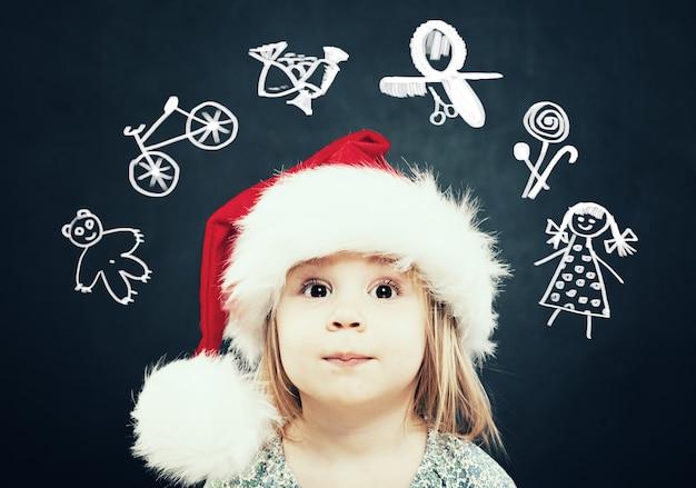 Маленькая девочка в шляпе санты мечтает о подарках. рождественский ребенок