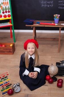 Маленькая девочка в школьной форме сидит в классе с будильником, яблоками и счетами