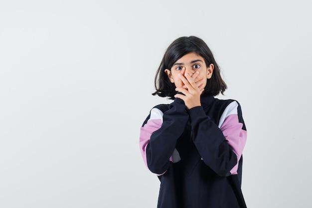 Маленькая девочка в рубашке, взявшись за руки рот и выглядя испуганной, вид спереди.