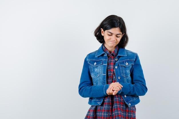 シャツを着た少女、手を握り締めて夢のように見えるジャケット、正面図。