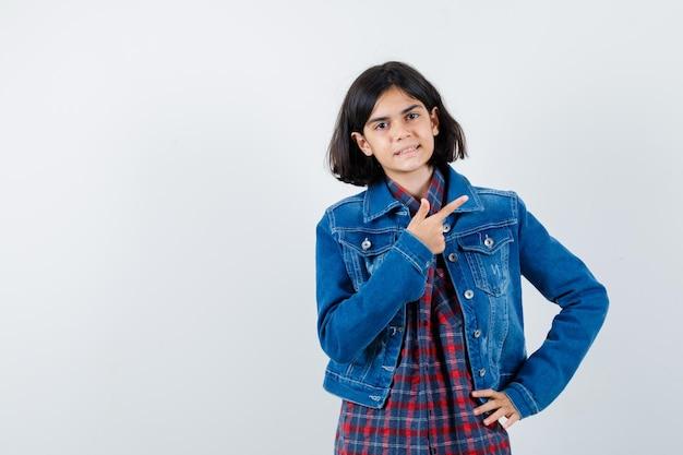 シャツを着た少女、右上隅を指し、自信を持って見えるジャケット、正面図。