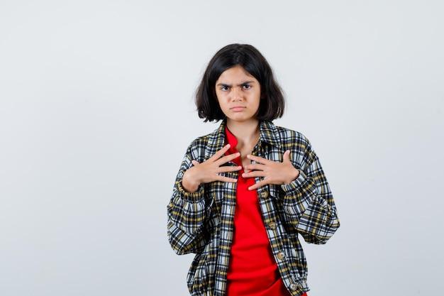 셔츠를 입은 어린 소녀, 재킷을 입고 자신을 가리키며 불만스러운 표정을 짓고 있습니다.