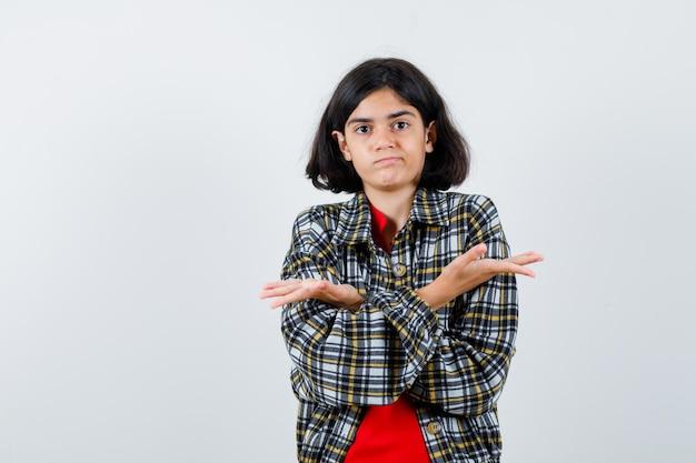 Маленькая девочка в рубашке, куртке показывает беспомощный жест со скрещенными руками и выглядит смущенным, вид спереди.