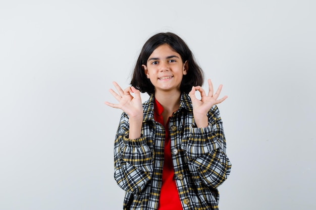 シャツを着た少女、大丈夫なジェスチャーを示し、嬉しそうに見えるジャケット、正面図。