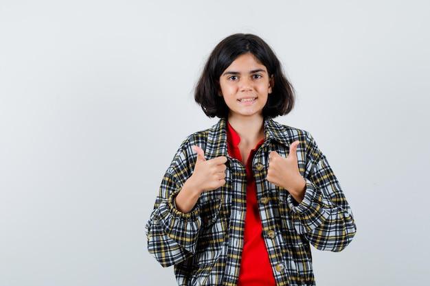 シャツを着た少女、親指を立てて満足そうに見えるジャケット、正面図。