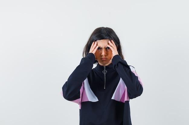 그녀의 이마를 문지르고 고통스러운, 전면보기를 찾고 셔츠에 어린 소녀.