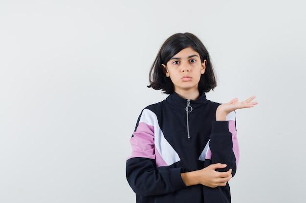 手のひらを脇に広げて困惑しているように見えるシャツの少女、正面図。