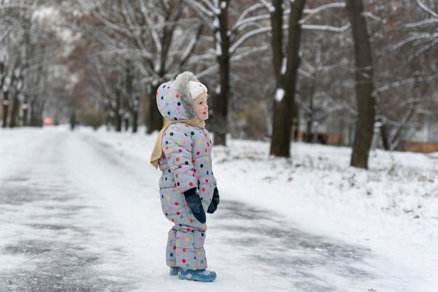 Snowsuit에 어린 소녀는 눈 덮인 공원에서 걷고있다. 겨울 날씨.
