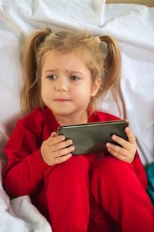 家で遊んでいる柔らかく暖かいパジャマの少女。カラフルな服を着て楽しんでいる白人の子供たち。
