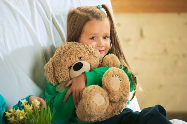 집에서 놀고 부드럽고 따뜻한 파자마에 어린 소녀.