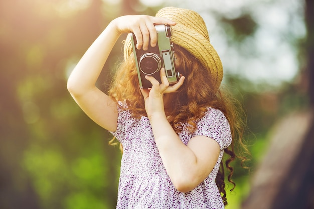 夏の公園でレトロな写真カメラで麦わら帽子、素朴なスタイルのドレスの少女。