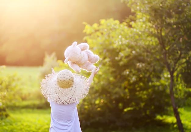 Маленькая девочка в соломенной шляпе ходит и играет со своим игрушечным медведем в летнем саду, освещенном теплым золотым светом заката.