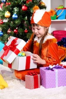 リスのスーツを着た少女がお祝いの装飾が施された部屋でギフトを開きます