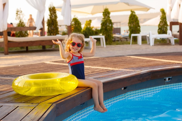 夏にプールのそばに座って、サングラスと水着の少女