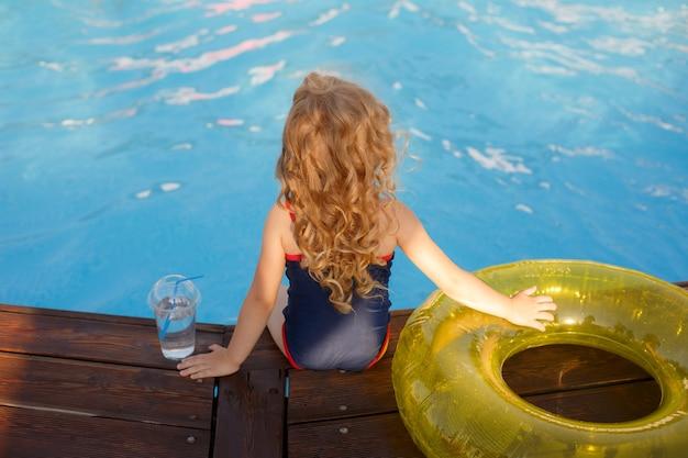 선글라스와 수영복에 어린 소녀, 여름에 수영장 옆에 앉아