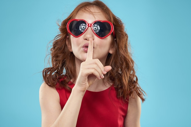 ハートの形のサングラスの少女赤いドレス巻き毛青い背景