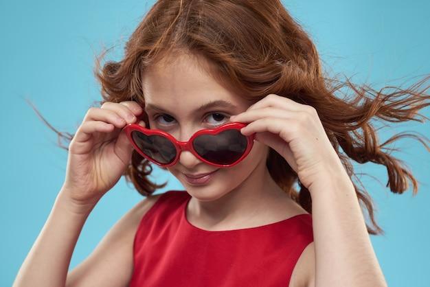 ハートの赤いドレス巻き毛の形でサングラスをかけた少女