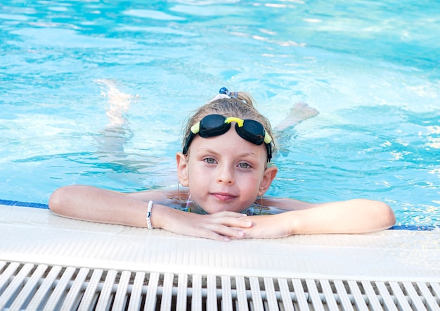 수영 고글을 쓴 어린 소녀가 수영장에서 수영한다