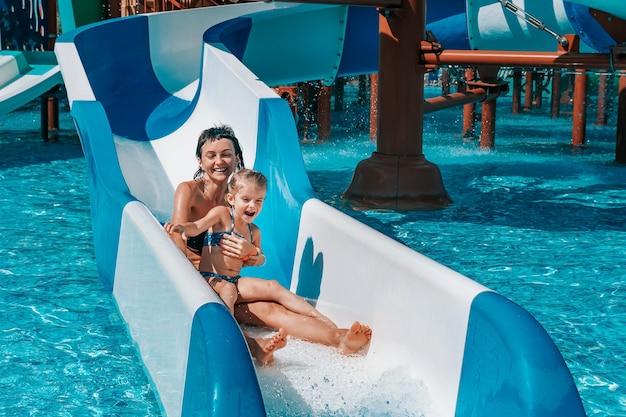 水着姿の少女が青いスライドを下ってプールに行き、ママと娘が屋外プールで遊んで泳ぐ