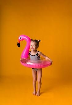 수영복을 입은 어린 소녀는 노란색 배경에 부풀릴 수 있는 원으로 서 있다